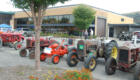 A shot of an assortment of classical tractors, red, orange, and rustic colors. The Museum is in the background.
